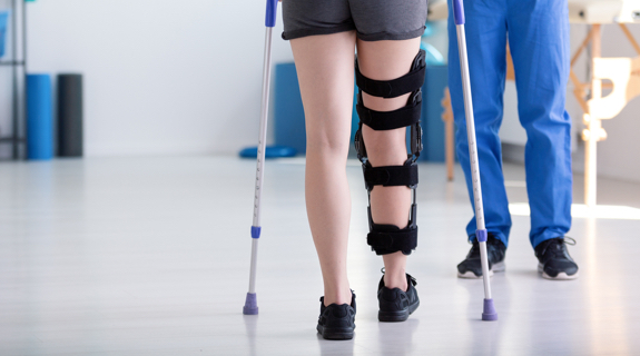 Person on crutches with leg brace in physical therapy